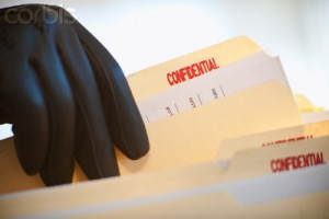 A gloved hand taking confidential files